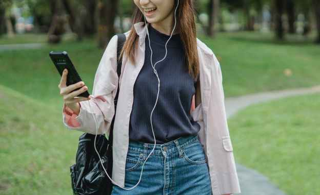 young female student making video call via black cellphone in park