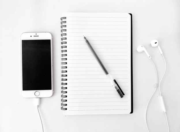 composition of notebook with pen near smartphone