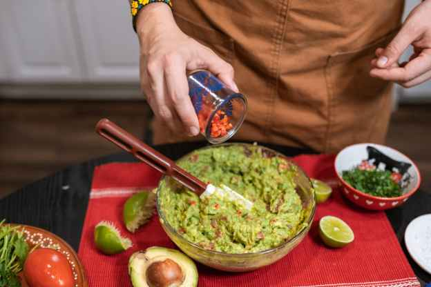 crop faceless person adding cut tomatoes in bowl with guacamole