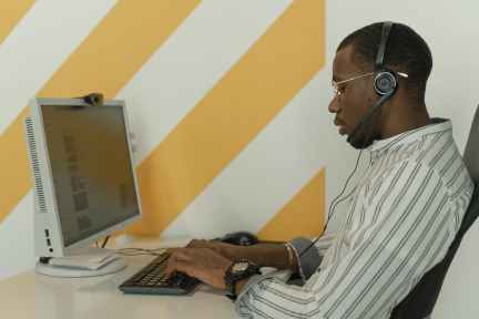 man in white and black stripe shirt using computer